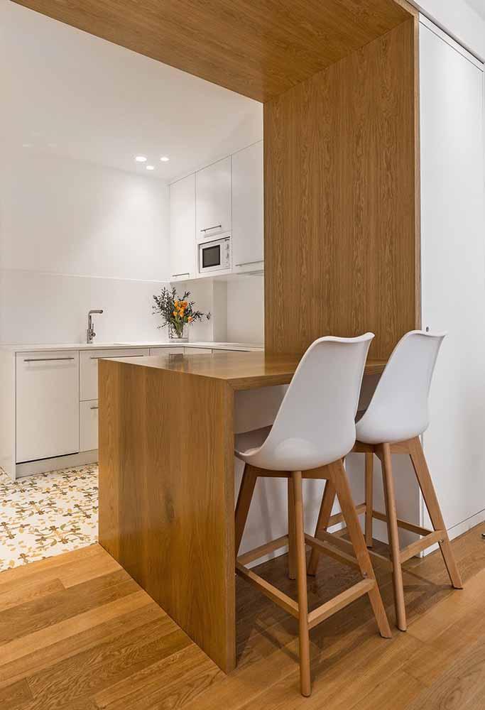 Cozinha simples em branco com uma bancada em madeira que vira espaço para refeições rápidas