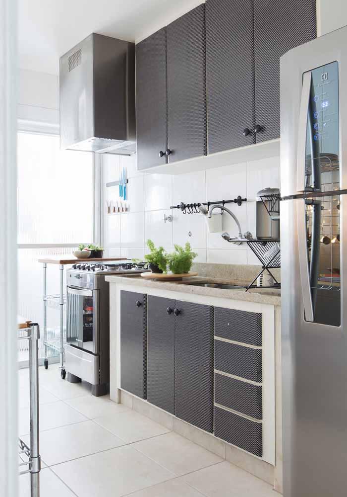 Uma ideia rápida e econômica para mudar um pouco a sua cozinha simples é apostar no envelopamento: neste caso, as portas dos armários já existentes ganharam mais destaque com adesivos alto-colantes aplicados