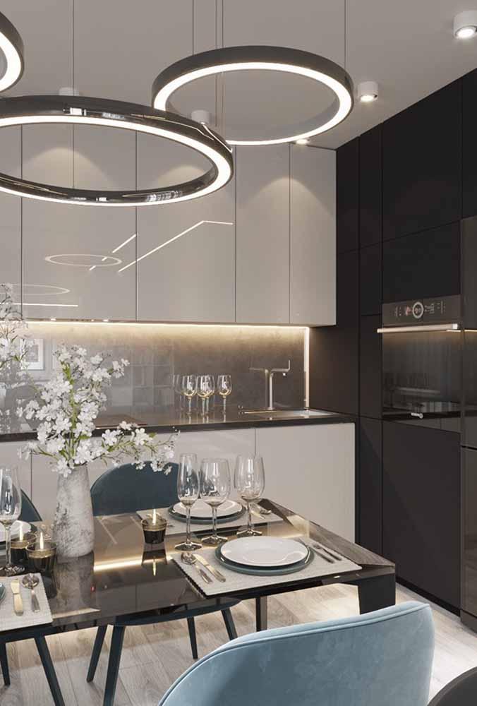 Pendentes modernos em forma de anéis, flores harmonizando com a cozinha branca e preta.