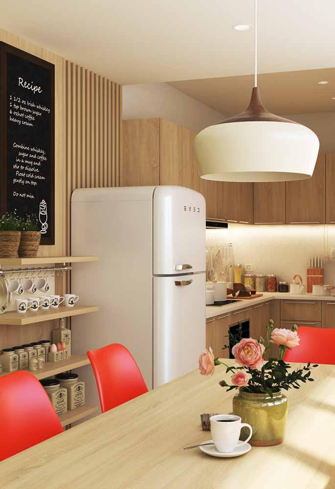 Decoração de cozinha em madeira e cadeiras em vermelho para contraste . Flores, quadro negro e pendente bonito e sofisticado