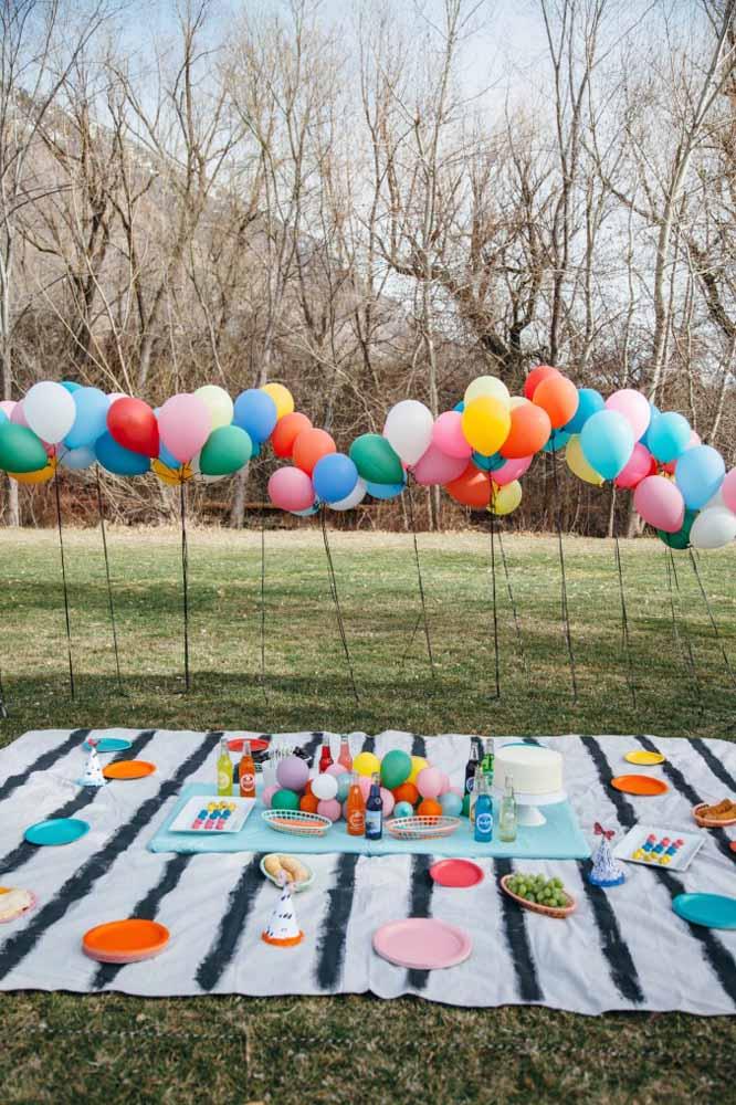 Reserve um cantinho no parque, coloque uma toalha, decore com itens coloridos e chama a criançada para fazer um piquenique diferenciado