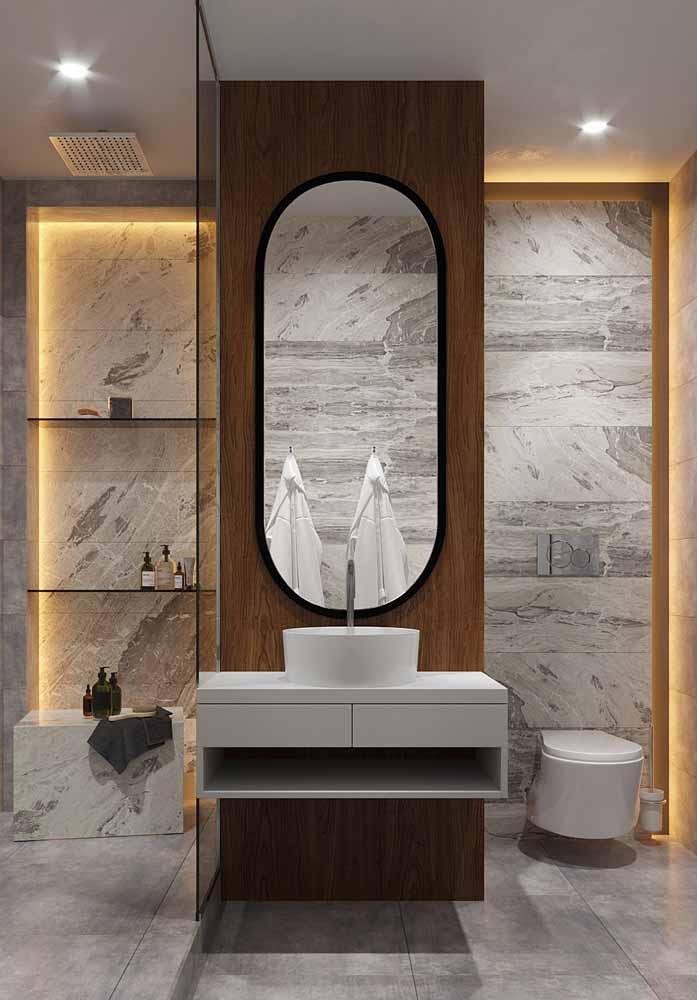 Neste banheiro, a fita de LED âmbar acompanhando os nichos na parede ajudam a dar um clima mais intimista para o ambiente