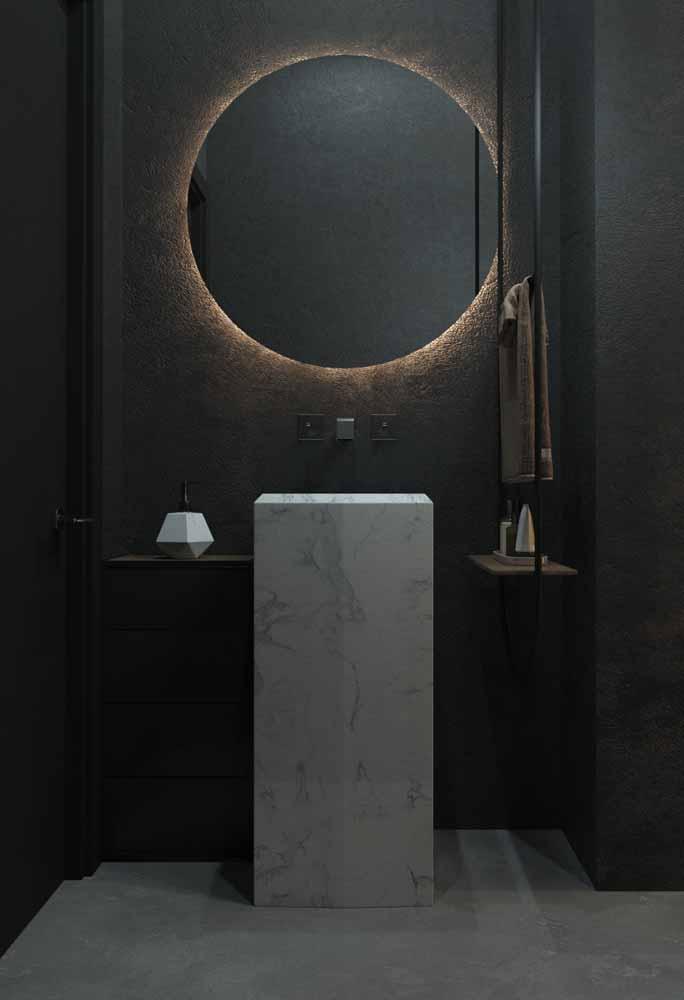 Num clima mais intimista, este espelho iluminado com LED âmbar ganha destaque no banheiro escuro e lembra um eclipse lunar