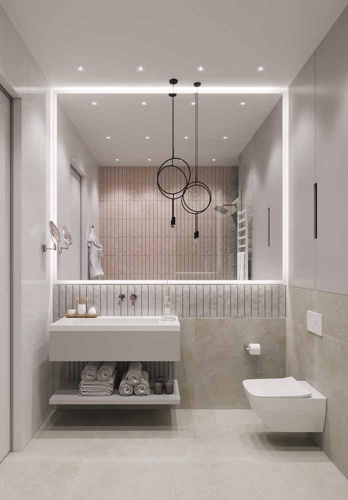 O espelho deste banheiro ganha mais destaque e ajuda a ampliar o espaço com a fita de LED branca ao redor