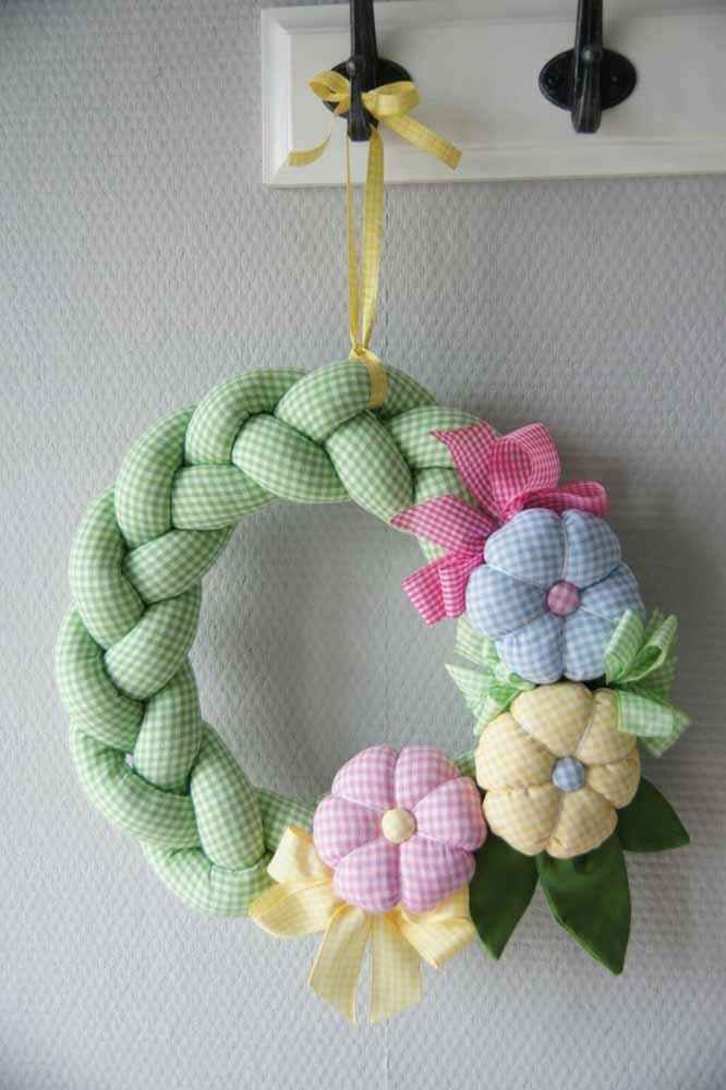 Flores de tecido com preenchimento em padrão colorido e xadrez nesta guirlanda para a porta do quarto do bebê
