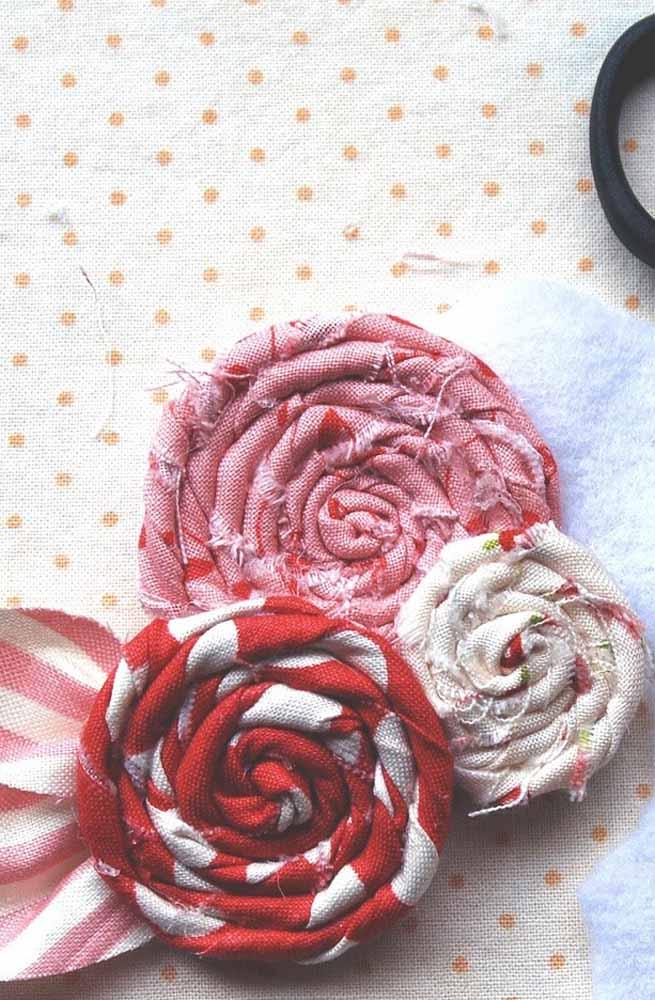 Num estilo pirulito, enrole tiras de tecido colorido para fazer flores redondas como estas