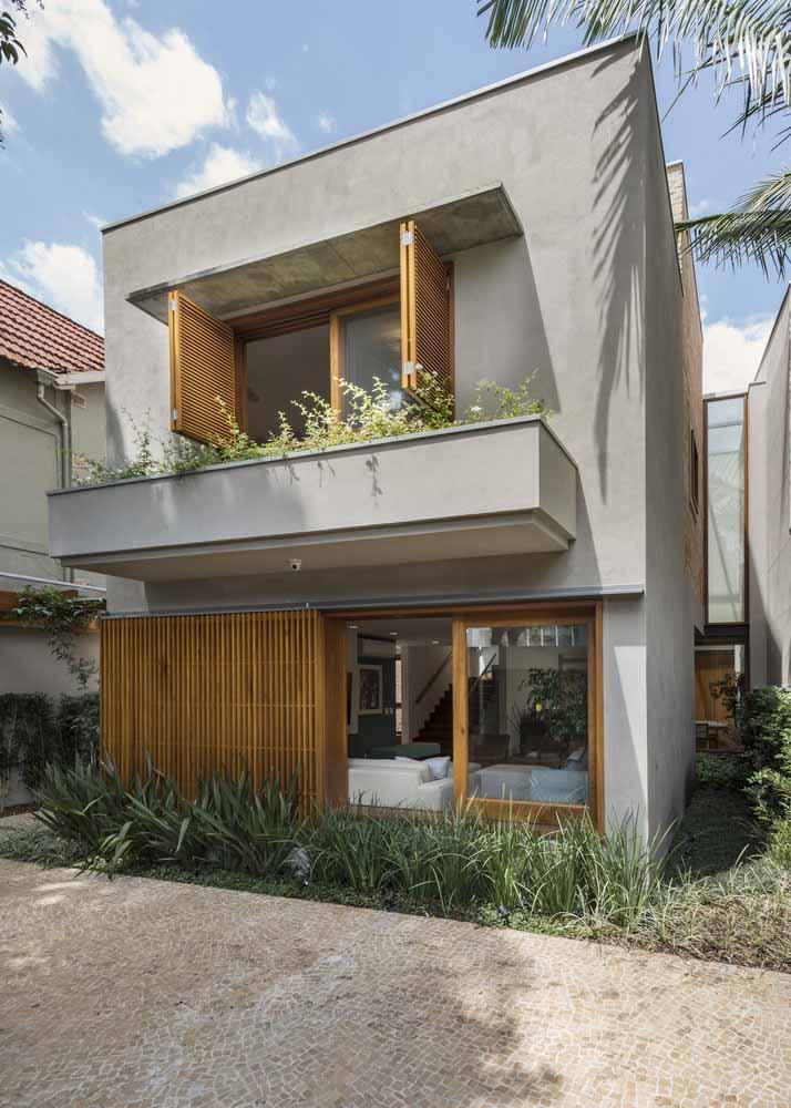 O cinza e a madeira marcam a fachada moderna e aconchegante do projeto do escritório Rocco Arquitetos
