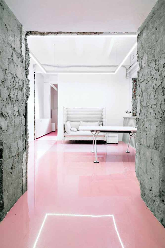 A delicadeza do rosa do porcelanato líquido em contraste com a parede rústica de cimento