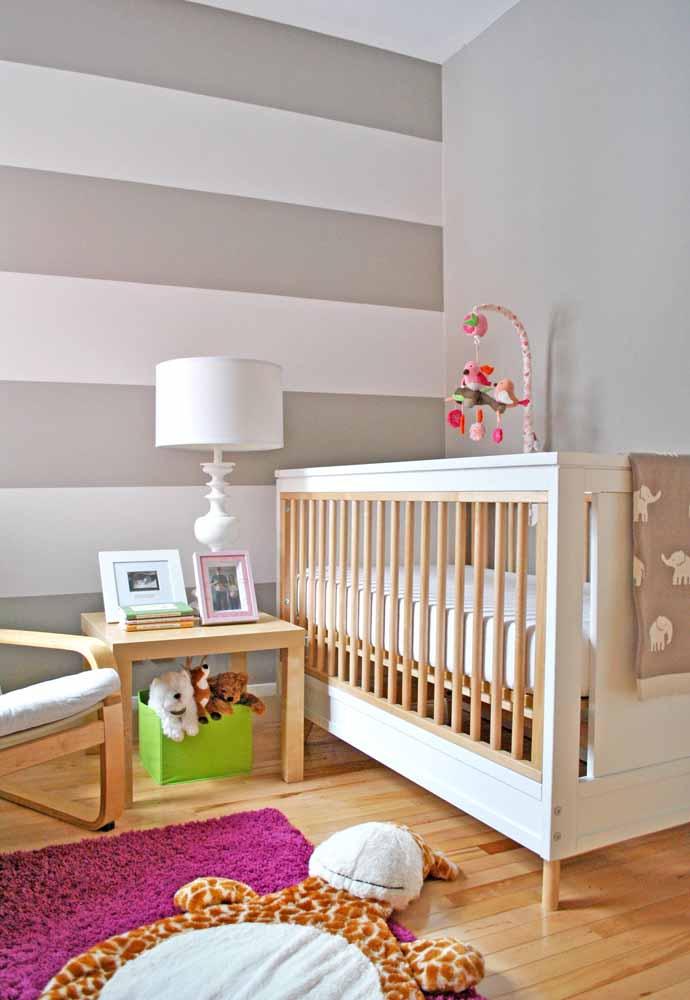 Neste quarto de bebê simples, as cores vibrantes aparecem no ambiente neutro a partir dos brinquedos e da decoração complementar