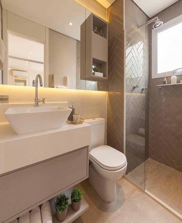 A prateleira baixa desse pequeno banheiro acomoda as toalhas e um discreto vasinho