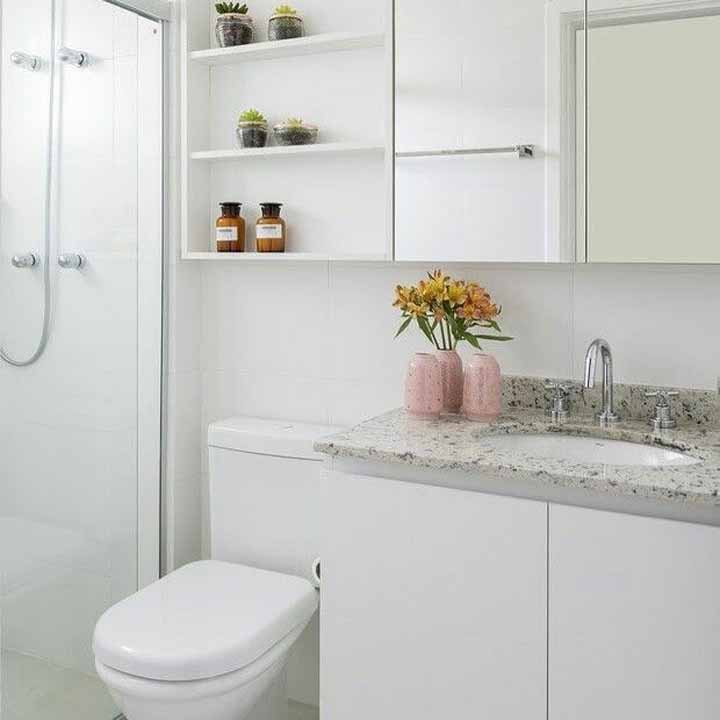 Banheiro branco simples decorado com vasinho discreto de flores amarelas