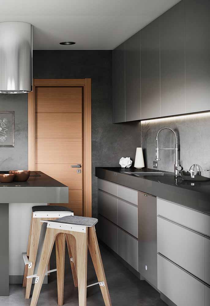 A parede de cimento queimado misturado com o armário na cor cinza fica um charme só. Para completar uma porta de madeira para destacar o lugar