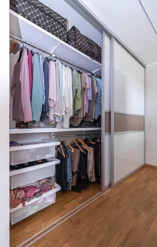 Guarda-roupa planejado de casal se estende por toda a parede do quarto, mas de modo muito clean e discreto
