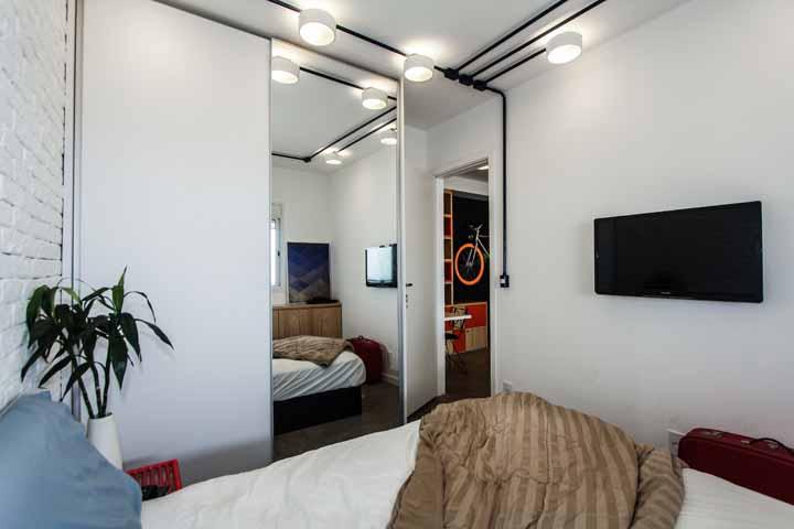 A porta de correr espelhada causa um efeito de amplitude interessante para esse quarto