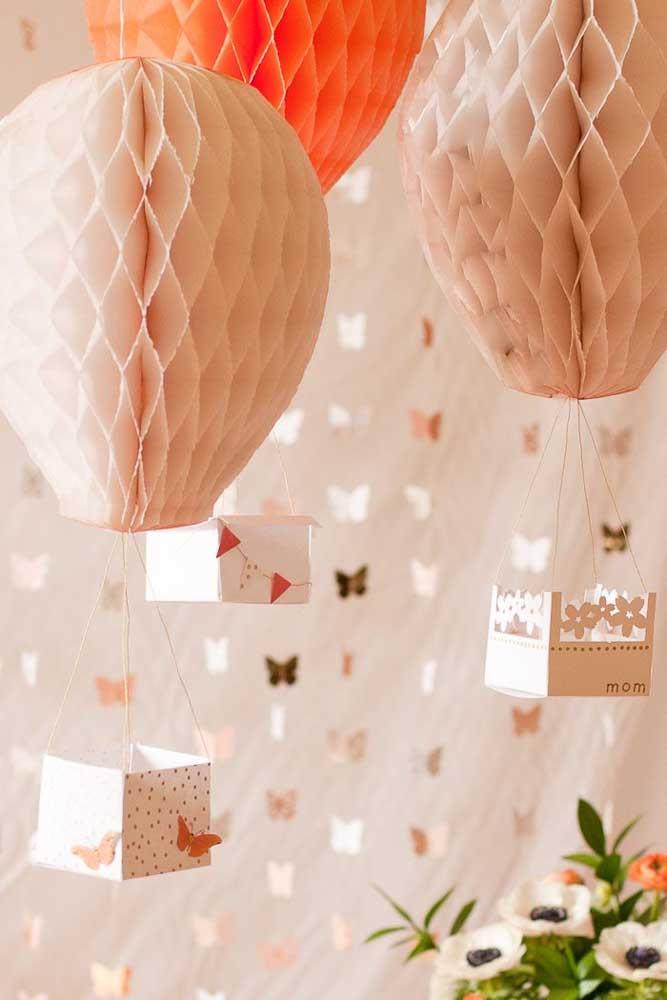 Para combinar com o painel cheio de borboletas, use balões suspensos no mesmo tom