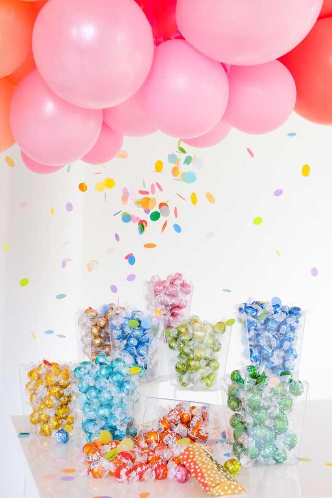 Pegue várias vasilhas transparentes e encha de bombons com embalagens coloridas