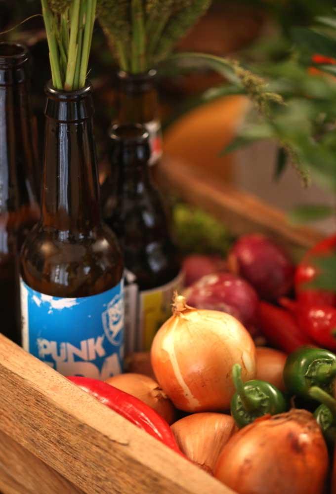 Uma boa opção de decoração é usar temperos, especiarias e até legumes para enfeitar caixotes. Aproveite algumas garrafas de cerveja para colocar os arranjos florais.