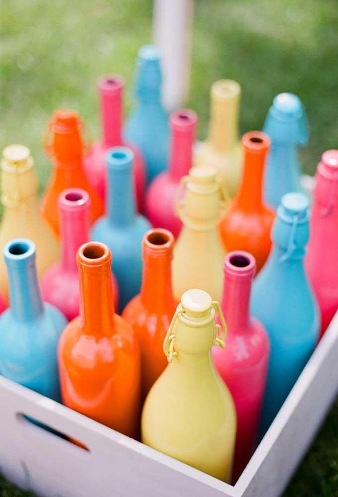 Para fazer uma decoração diferente, recicle algumas garrafas e pinte nas cores de sua preferência