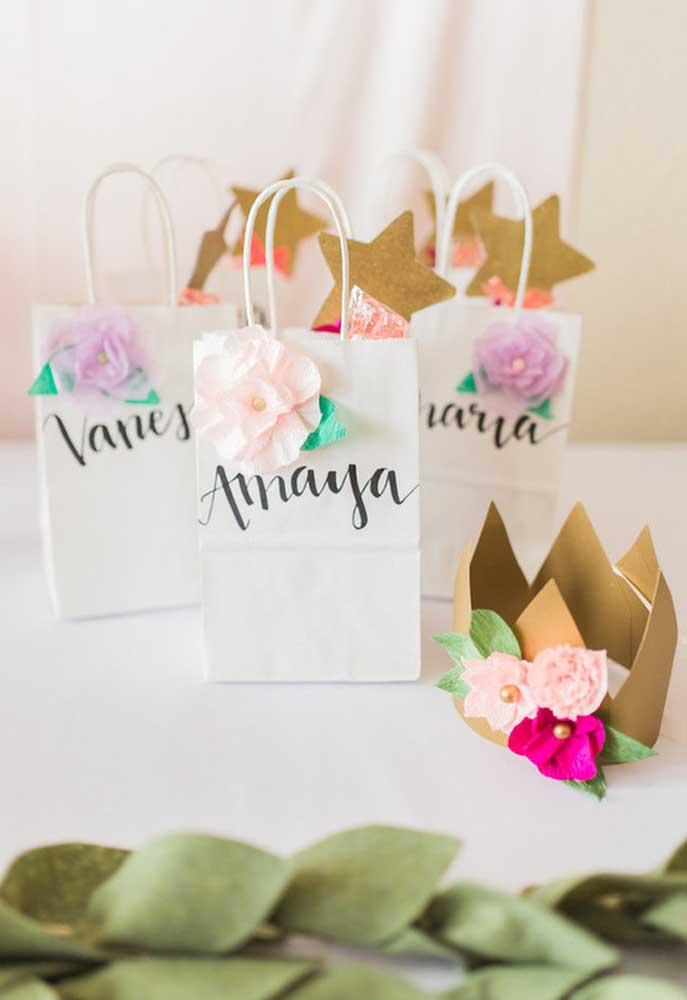 Você pode encontrar saquinhos de papel em várias lojas de festas e aproveite que são bem baratas. Para dar um toque especial, coloque uma rosa de papel na frente e escreva o nome de cada convidado