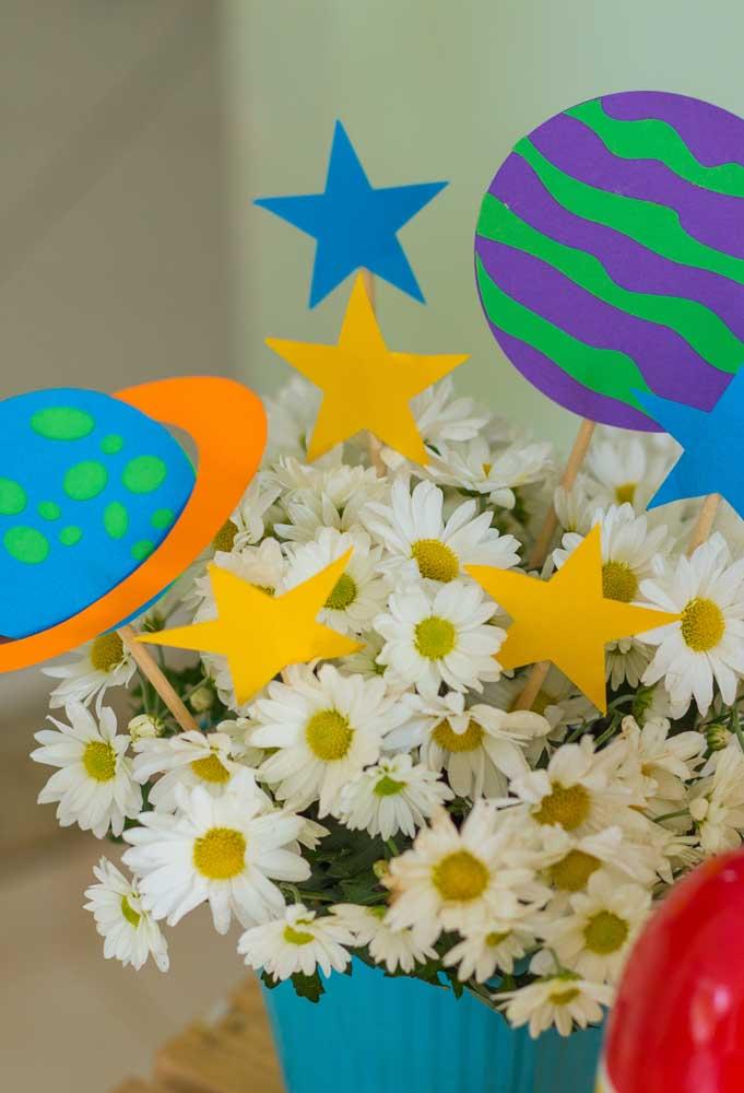 Prepare um arranjo com flores artificiais e com elementos do tema da festa feitos de papel