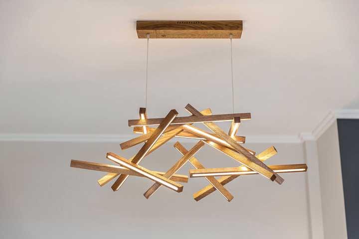 Luminária de madeira feita com várias ripas que flutuam no ar