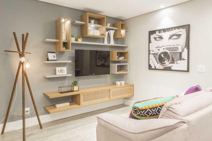 A luminária de madeira de piso é o grande destaque dessa sala de estar