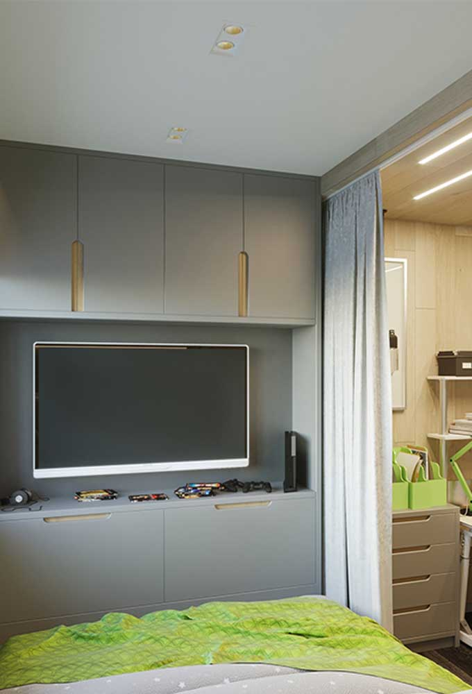 Ao invés de colocar um rack no quarto para colocar a TV, use uma estante com uma cor sóbria para combinar com a decoração do cômodo.