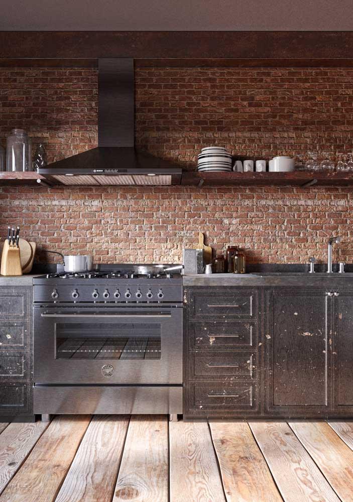 Rústica e moderna: tijolinho aparente na parede da cozinha e piso de madeira para completar a proposta, entre eles armários pretos e eletros de inox para dar o toque de modernidade ao conjunto