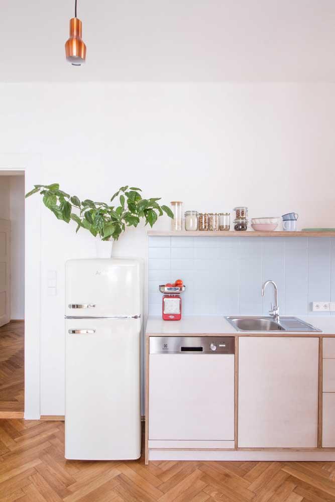 Já aqui, são os azulejos de metro azul claro que protegem e decoram a parede; no chão o piso de madeira reforça a influência retrô da cozinha