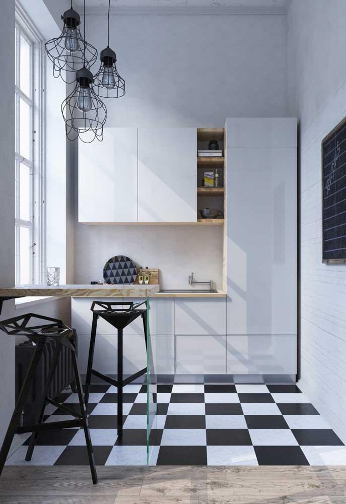 Piso vinilico xadrez preto e branco para marcar a área da cozinha; na parede, apenas tinta branca