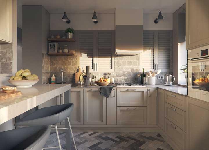 As pedras brutas na parede completam a proposta cinzenta da cozinha