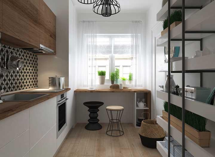 Tudo se encaixou perfeitamente nessa cozinha: o revestimento preto e branco na parede, o piso amadeirado e o tom dos armários