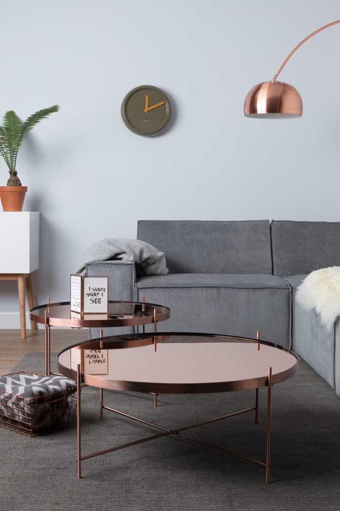 Nessa decoração a luminária e a mesa de centro fazem um contraste com o sofá e tapete cinza