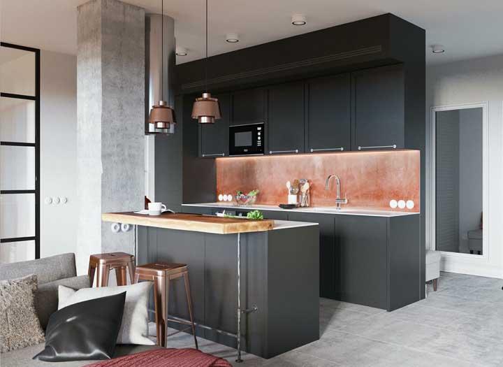 Em uma cozinha decorada no tom escuro, um papel de parede na cor rosé gold quebra toda a sobriedade do local