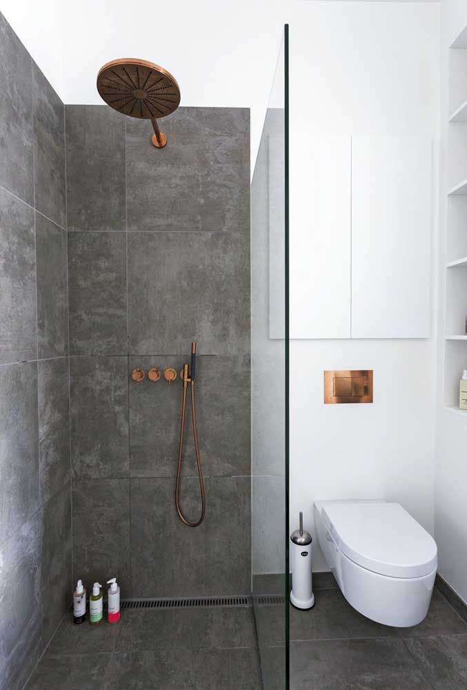 Nos detalhes do banheiro como o chuveiro e porta papel higiênico, você pode usar a cor rosé gold para fazer um contraste com o resto da decoração