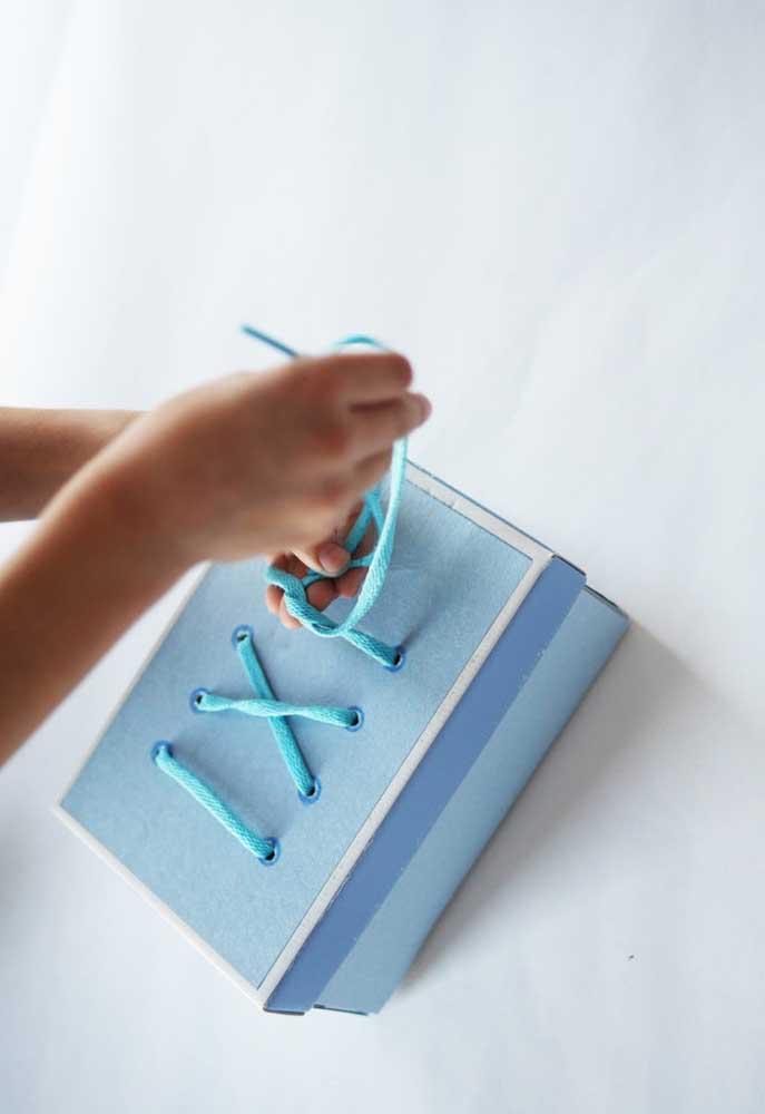 Para customizar a caixa de sapato, use diferentes materiais. Nesse caso, o objetivo é como se estivesse amarrando o cadarço do tênis.
