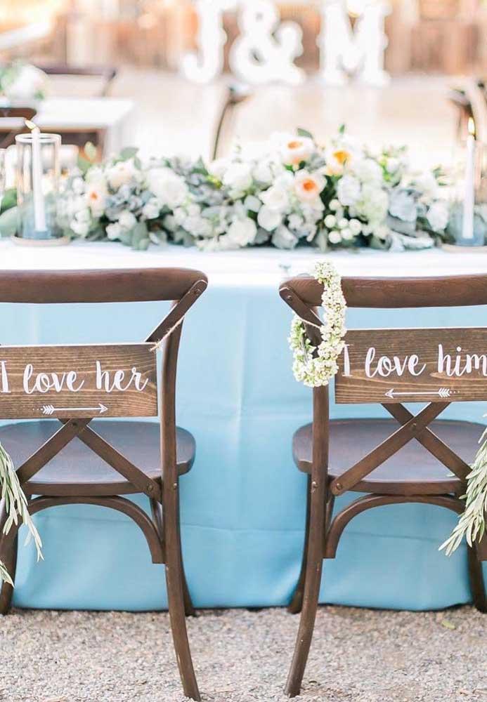 Casamento na praia decorado com tons suaves de azul, flores brancas e móveis de madeira