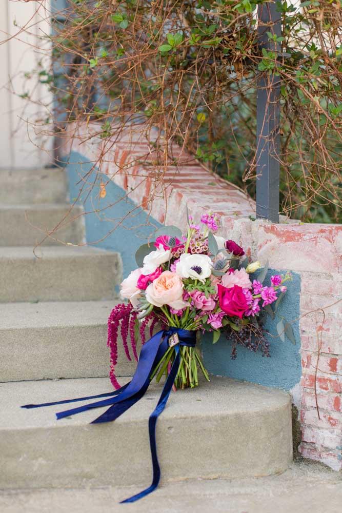 O laço azul dá o toque final ao buquê cor de rosa