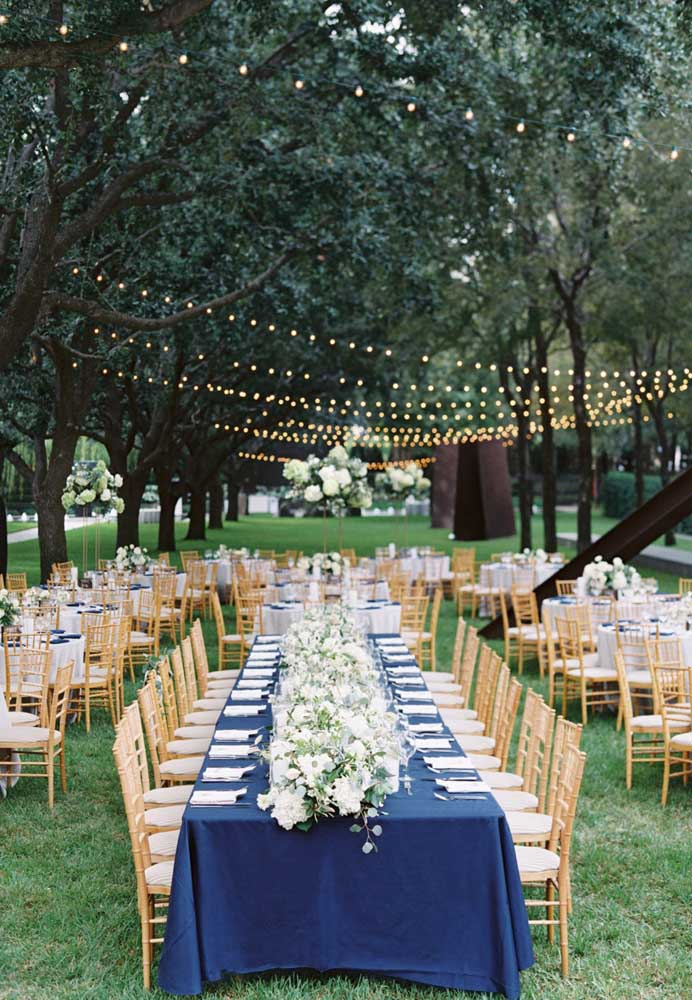 A mesa principal dessa festa foi decorada com uma enorme e elegante toalha azul royal; para as mesas menores, toalhas brancas com detalhes em azul