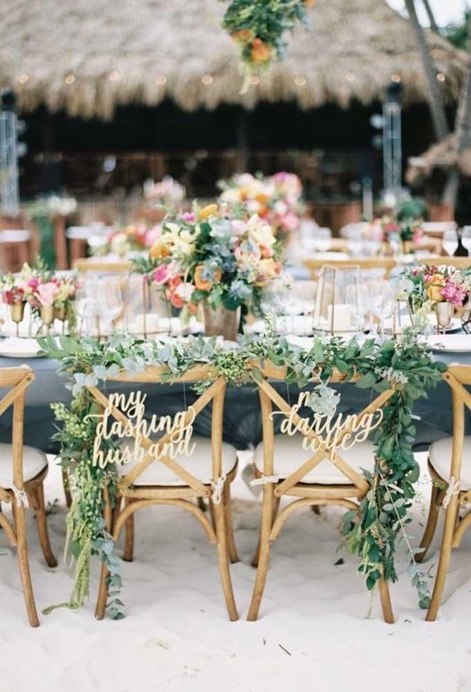 Na mesa principal, reserve as cadeiras dos noivos. Para isso, identifique cada uma das cadeiras e faça um belo arranjo.