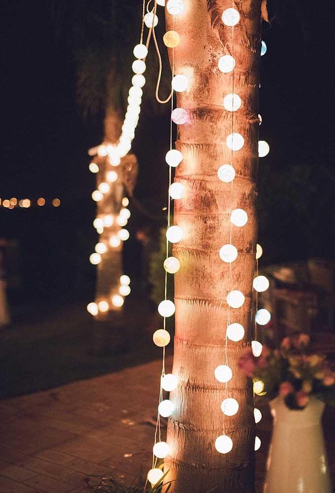 Pendure luzes nos troncos das árvores para iluminar o ambiente.
