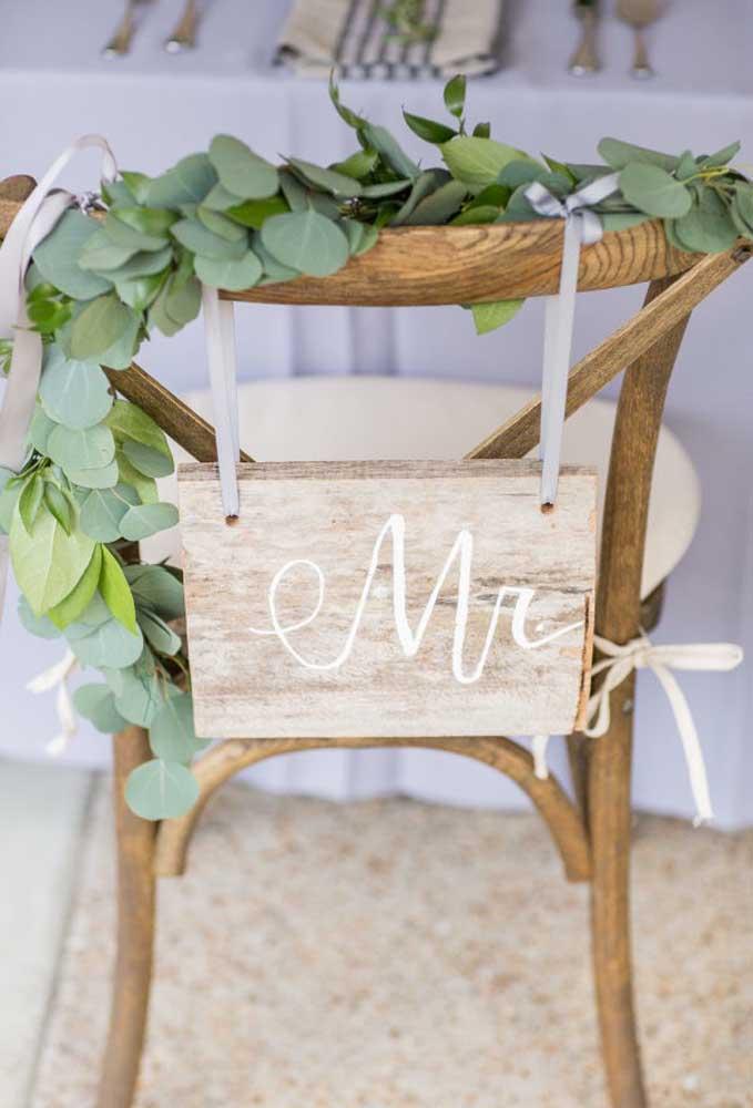 Em uma festa de casamento com muitos convidados, é necessário reservar os assentos dos noivos. Para decorá-los, use alguns arranjos com folhas e coloque uma plaquinha feita de madeira com a identificação.