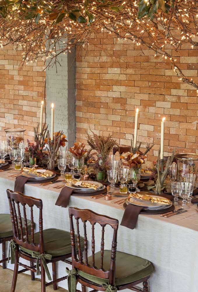 As velas devem iluminar a mesa dos convidados, mas para ficar ainda mais encantador, coloque algumas luzes nos galhos das árvores.