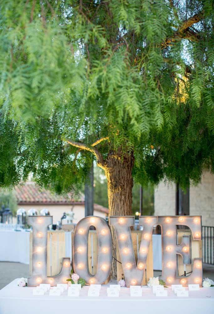 Que tal preparar uma bela mesa aos pés da árvore? Uma boa opção é usar as letras iluminadas para destacar o espaço.