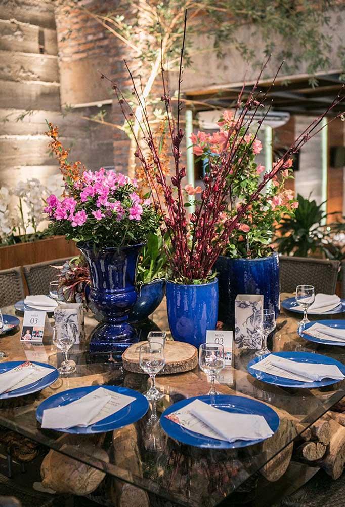 O pé da mesa é todo feito com troncos de árvore. O charme ficou pela mesa de vidro, destacando esse detalhe.