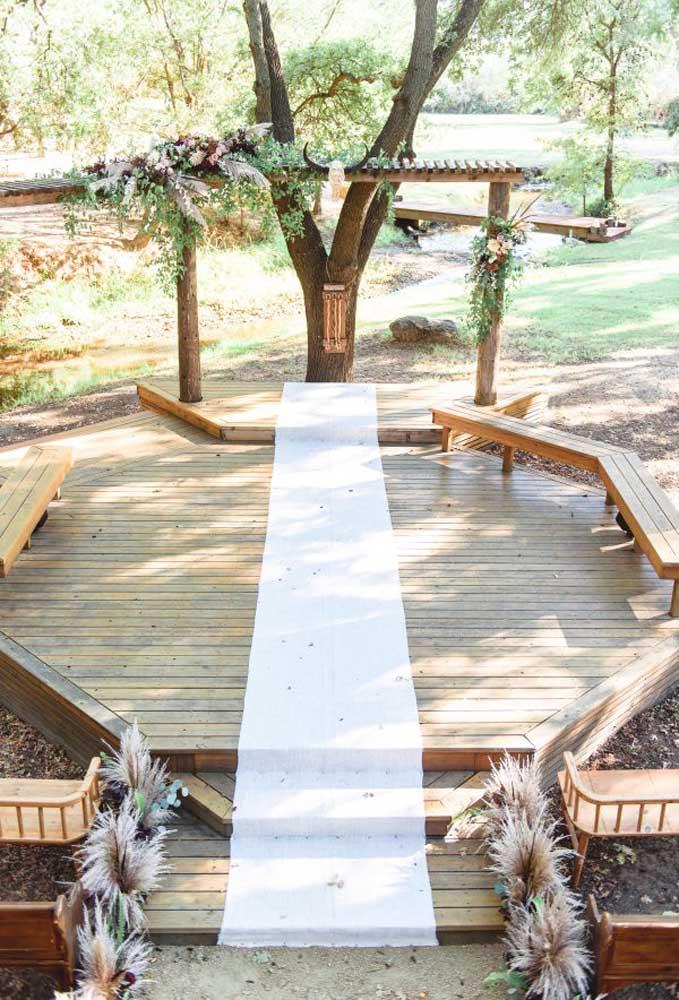 Para fazer a cerimônia de um casamento rústico você pode decorar o espaço com alguns bancos de madeira que são indicados para os padrinhos se sentarem, um belo tapete e uma simples capelinha.