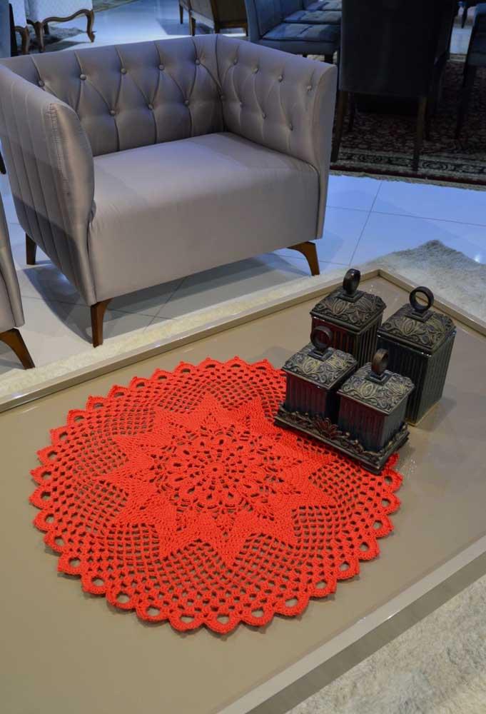 Para destacar a mesa de centro da sala, faça um centro de mesa de crochê usando cores fortes como o laranja.