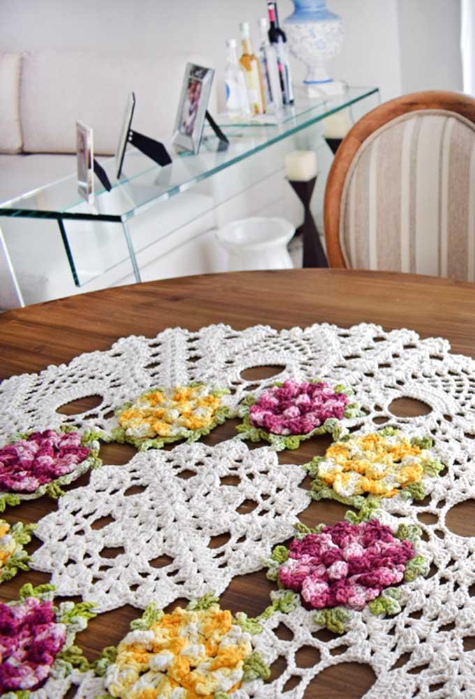 Se a intenção é deixar o ambiente mais romântica, acrescenta algumas flores no desenho do centro de mesa de crochê.