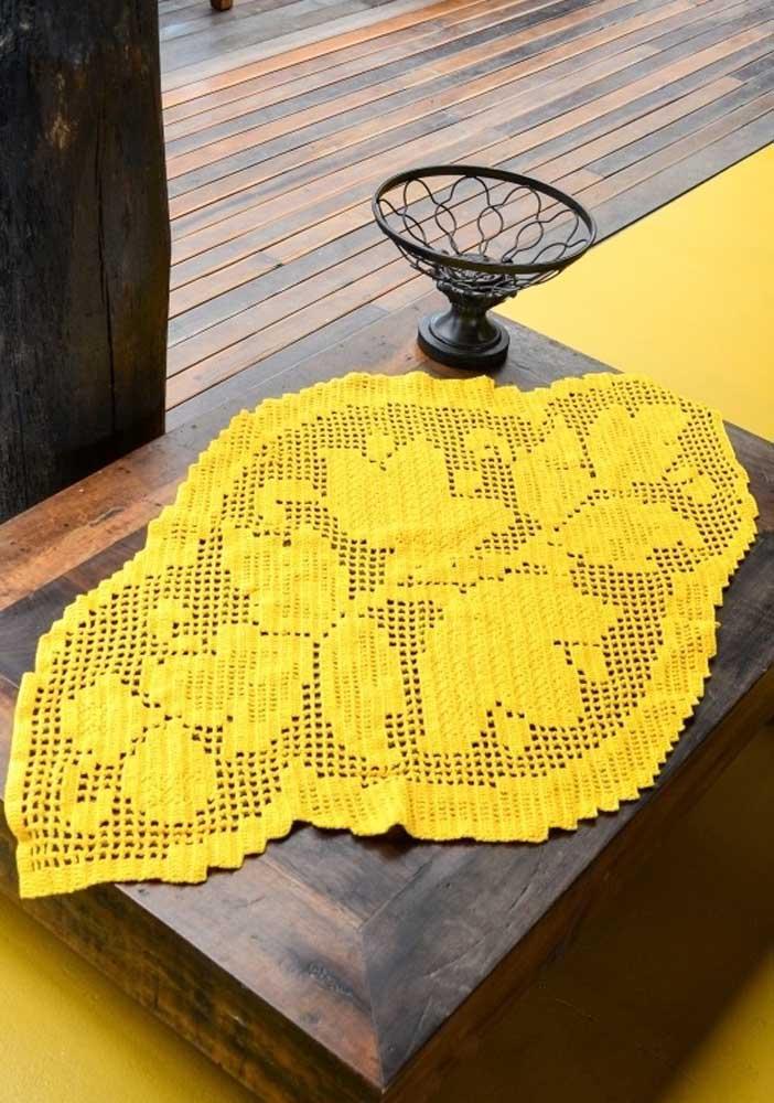 O centro de mesa de crochê feito com fios brancos fica ainda mais lindo com os detalhes de flores.