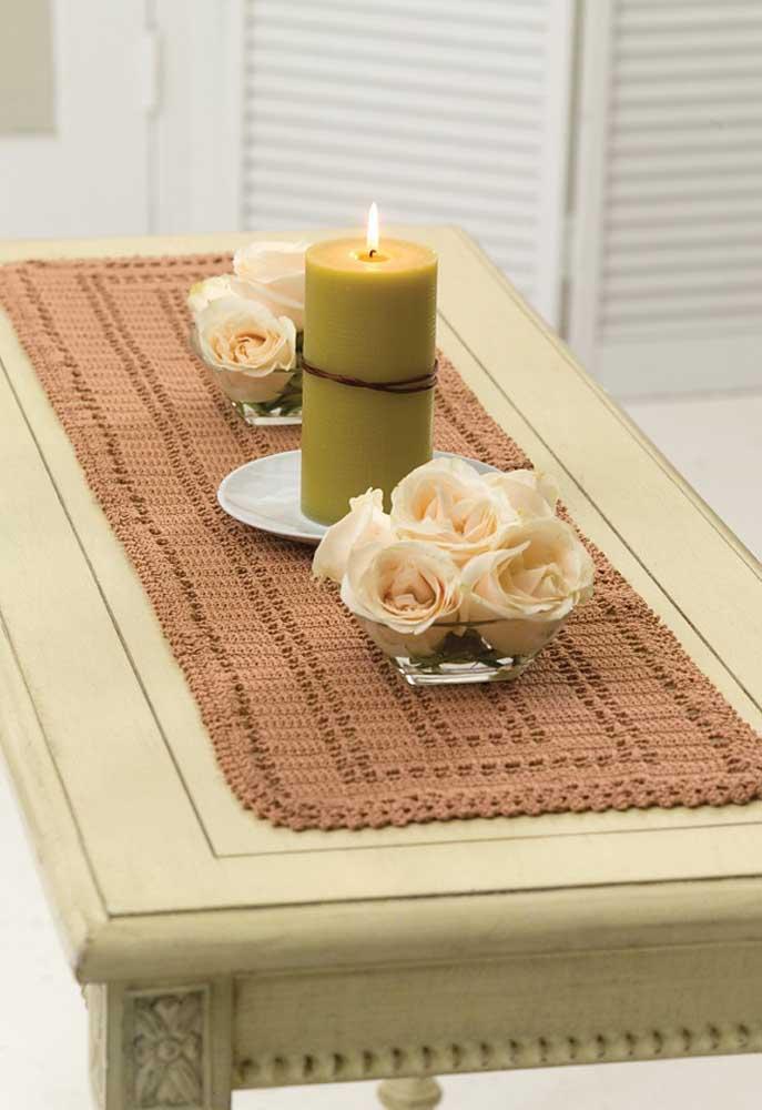 Aposte em um centro de mesa de crochê na cor marrom para contrastar com a mesa mais clara.